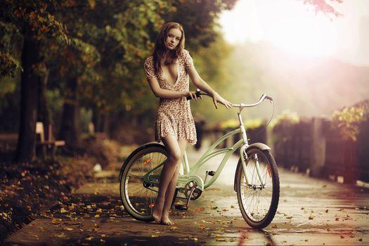 В платье под дождем девушка с велосипедом