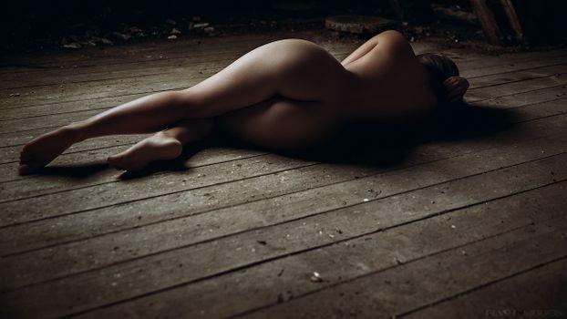 Голая девушка лежит на деревянном полу