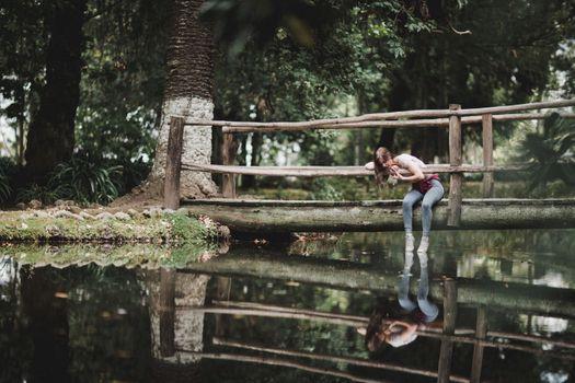 Бесплатные фото женщины,модель,брюнетка,урожай,джинсы,беседа,сидя,мост,отражение,вода,женщины на открытом воздухе
