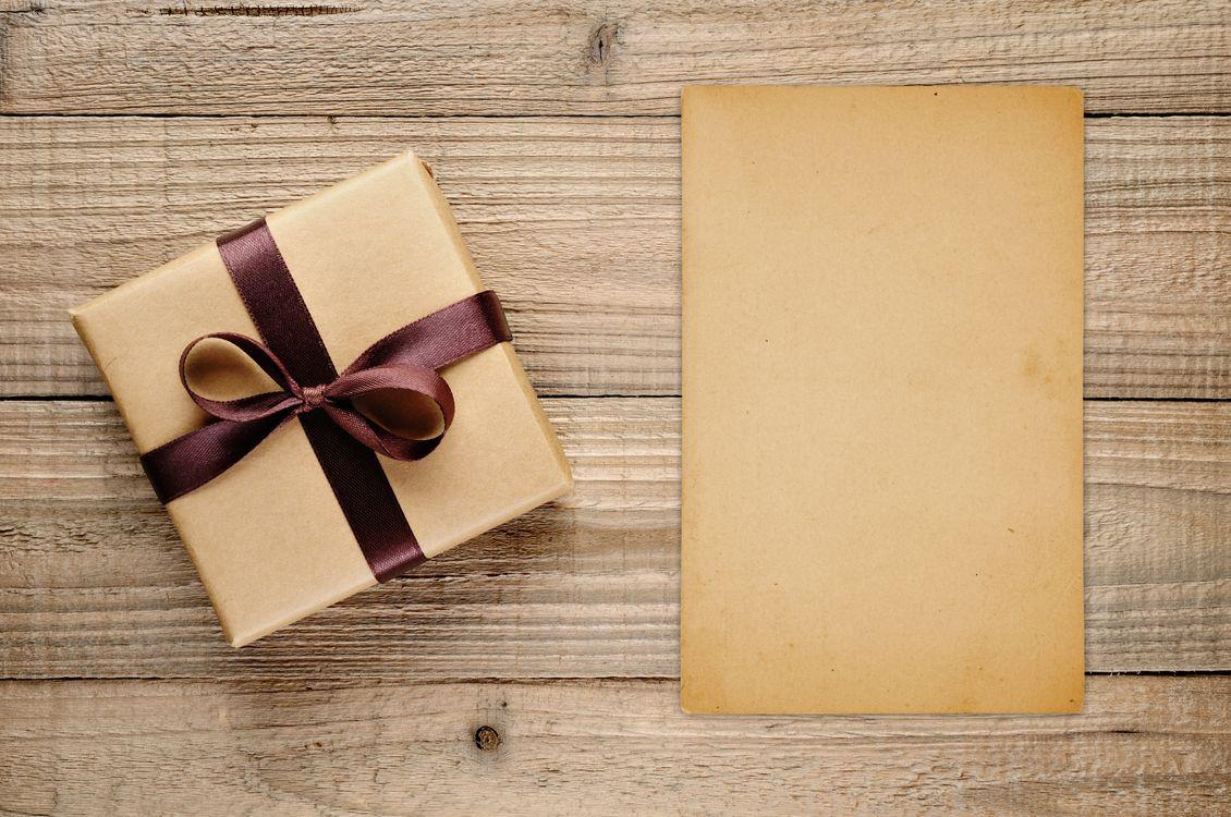 Фото бесплатно подарок, лента, коробка, лист бумаги, деревянный пол - на рабочий стол